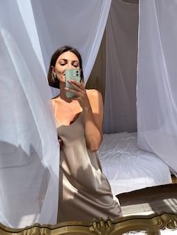 Una donna abbronzata in forma in un romantico abito di seta beige a casa scatta una foto selfie al telefono allo specchio