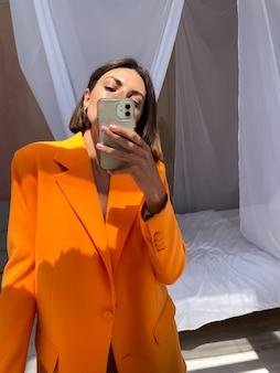 Una donna abbronzata in forma in un romantico abito di seta beige e un blazer arancione a casa scatta una foto selfie al telefono allo specchio