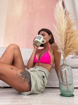 Donna abbronzata in forma con un corpo perfetto in pantaloncini e bikini che tiene tazza