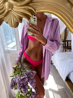 Fit tanned woman with perfect body takes photo selfie on phone in mirror at home