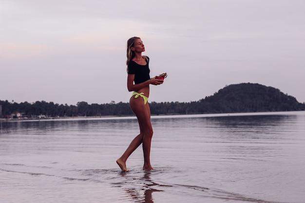 日焼けした若い白人女性を日没時に海に合わせる