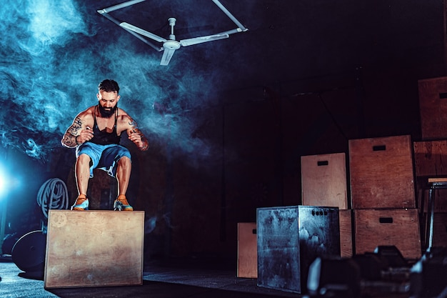 Fit tattoed bearded man jumping onto a box as part of exercise routine. man doing box jump in the gym. athlete is performing box jumps