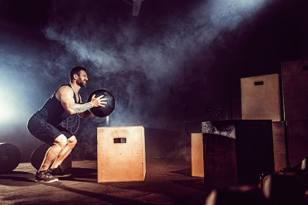 Fit tattoed bearded man jumping onto a box as part of exercise routine. man doing box jump in the gym. athlete is performing box jumps.