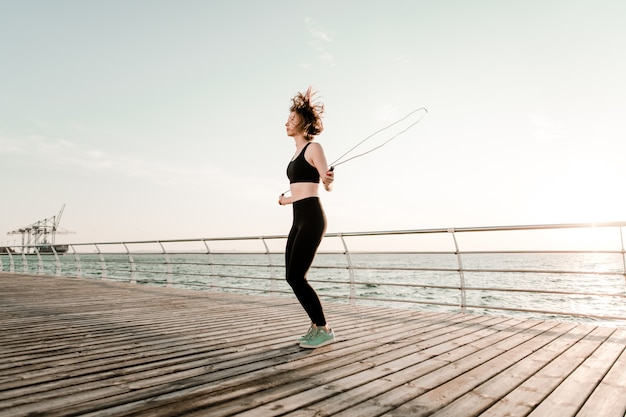 Fit teenage girl with jump rope on a beach exercising and working out