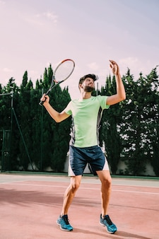 Fit tennis player serving