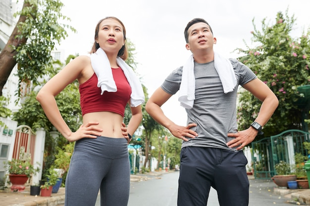 Fit tired young couple of runners