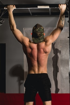 Fit toes to bar man pull-ups bars workout exercise at gym