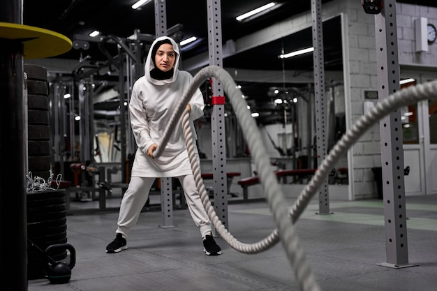Fit and toned muslim sportswoman working out in functional training gym doing crossfit exercise with battle ropes, wearing sportive hijab. cross-fit workout motivation