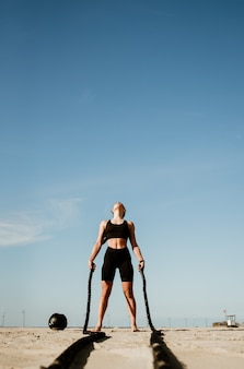 Fit and toned sportswoman working out in functional training gym at the beach