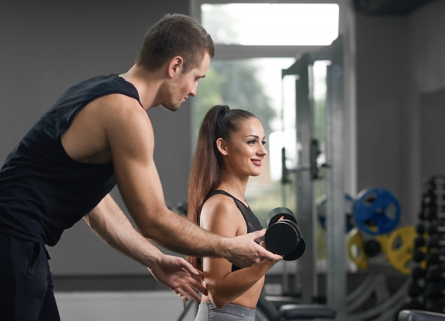 Fit trainer helping  and supporting energetic sporty girl.