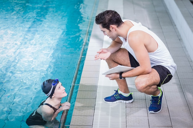Fit trainer talking to swimmer in leisure center