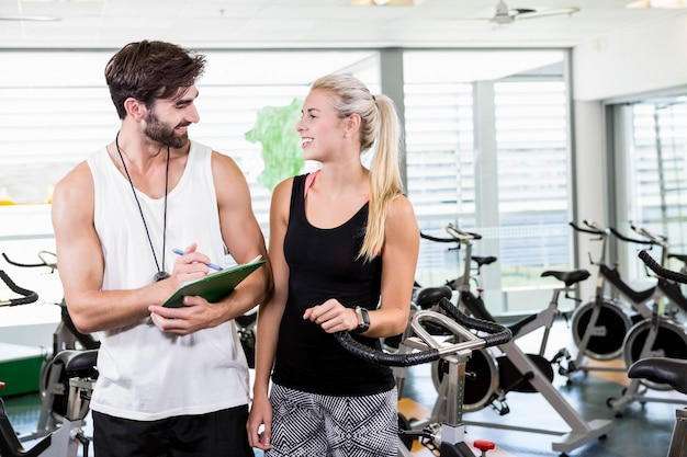 Fit trainer and woman talking at the gym