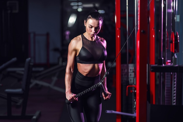 Fit well-trained woman workout triceps lifting weights in gym. athletic sexy woman doing exercise using machine in gym
