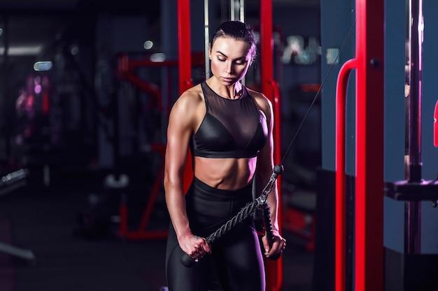 よく訓練された女性のトレーニング上腕三頭筋をジムでウェイトリフティングに合わせます。ジムでマシンを使用して運動をしている運動セクシーな女性