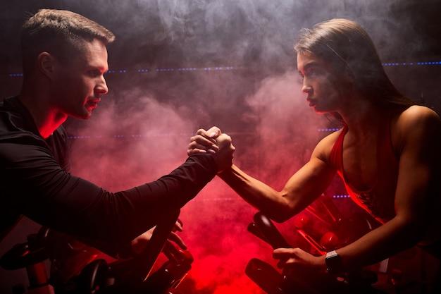 실내 스마트 고정식 자전거 훈련, 빨간색 연기가 자욱한 공간에서의 스포츠 경쟁에 맞는 여성과 남성. 팔씨름