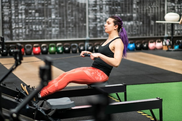 Fit woman athlete working out on a rowing machine