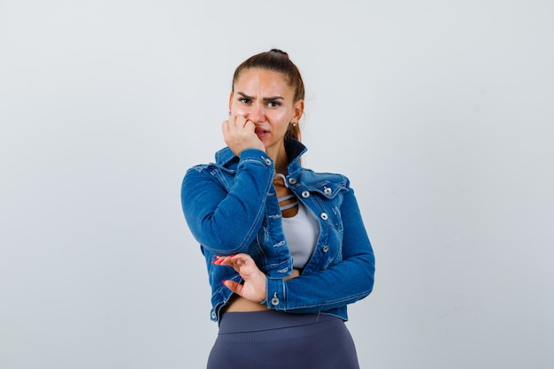 Fit woman biting fingers emotionally in crop top, jean jacket, leggings and looking anxious , front view.