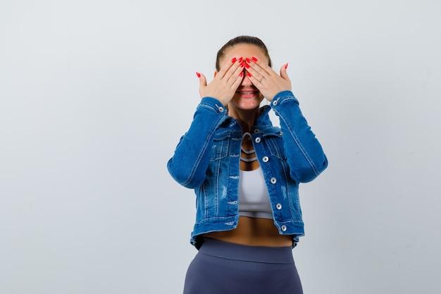 Donna in forma che copre gli occhi con le mani in top corto, giacca di jeans, leggings e sembra allegra, vista frontale.