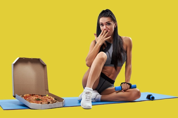 Fit woman covering mouth with her hand while sitting on a fitness mat near a box with tasty pizza and holding a dumbbell in the other hand. isolated portrait