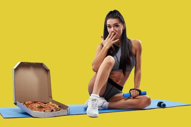 おいしいピザの入った箱の近くのフィットネスマットに座って、もう一方の手にダンベルを持って、手で口を覆っている女性にフィットします。孤立した肖像画