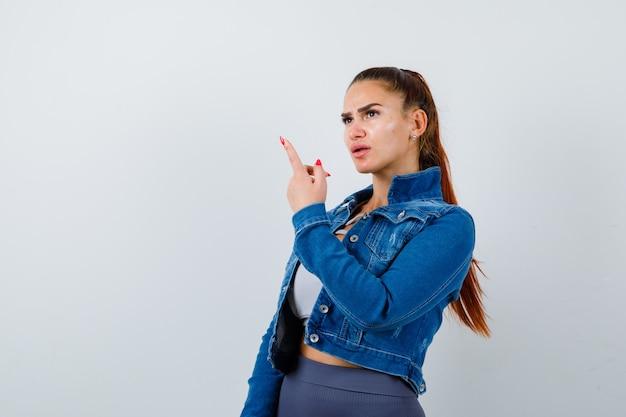 Fit donna in crop top, giacca di jeans, leggings che puntano verso l'alto con il dito indice e sembrano concentrati, vista frontale.