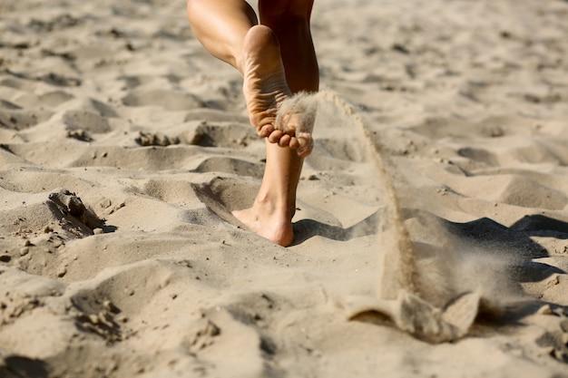 ビーチで有酸素運動をしている女性に合います。彼女の足のクローズアップショット
