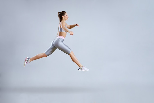 Fit woman doing cardio training in gym. woman in sportswear is jumping. fitness club concept. isolated on gray.
