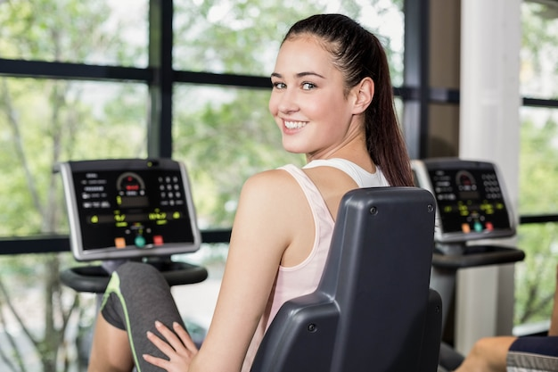 Fit woman doing exercise bike at gym