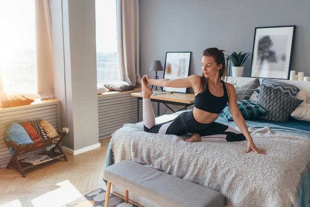 自宅のベッドで運動をしている女性に合う。