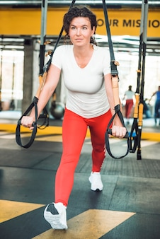 Fit woman doing exercise with fitness strap