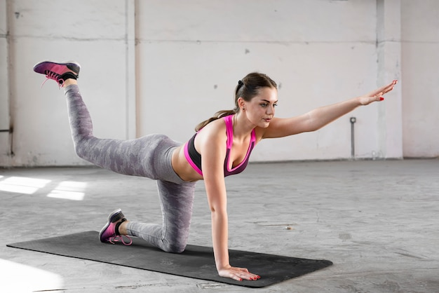 Fit woman doing exercise on yoga mat
