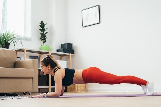 Подходит женщина упражнения планка дома.