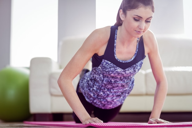 Fit woman doing press up on exercise mat