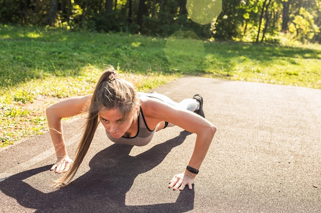 Fit woman doing pushups at the park.