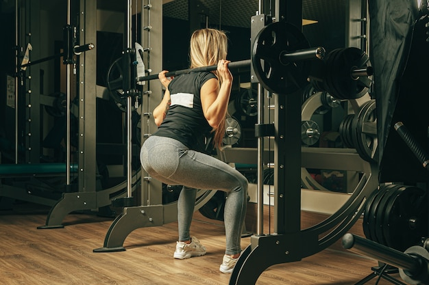 Fit woman doing squats in a smith machine in gym