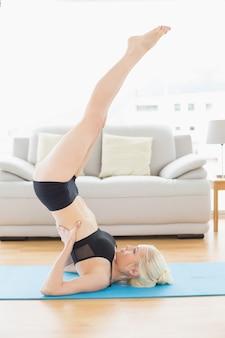 Подходящая женщина, занимающая позицию в плечевой стойке в фитнес-студии