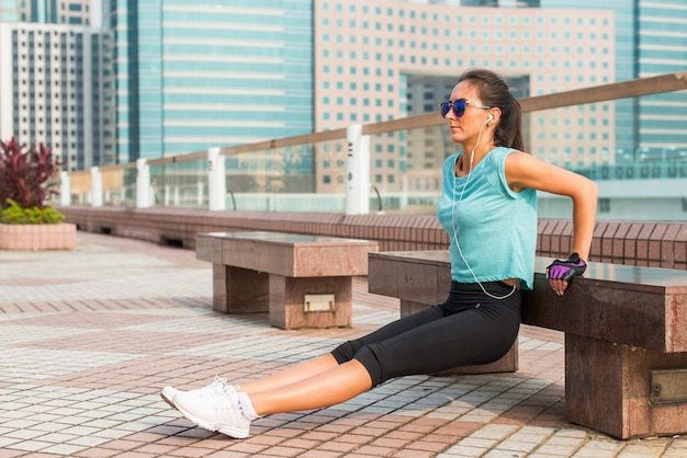 Fit woman doing triceps bench dips exercise while listening to music in headphones. fitness girl working out in the city