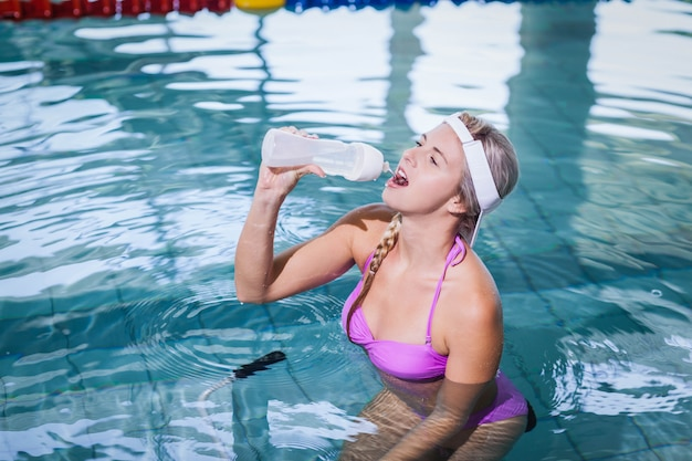 Fit woman doing underwater bike and drinking water at the pool