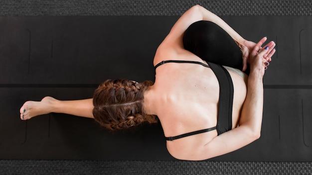 Подходящая женщина занимается йогой дома на коврике для йоги