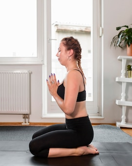 Fit woman doing yoga at home and sitting sideways