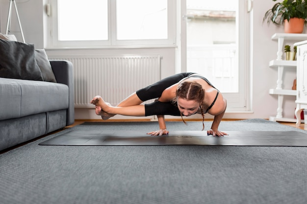 Fit woman doing yoga at home standing in her hands