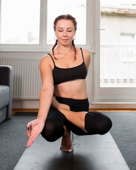 Fit woman doing yoga indoors