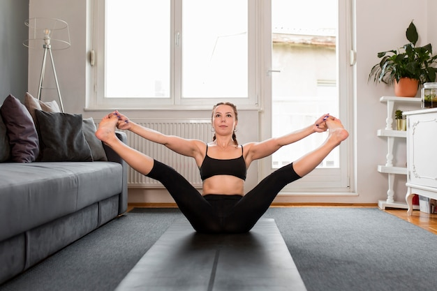Fit woman doing yoga and stretching her legs at home