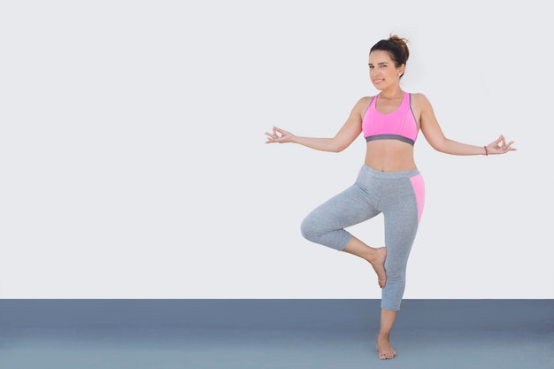 Подходящая женщина одетая для спорта в позиции йоги, изолированной на белизне.