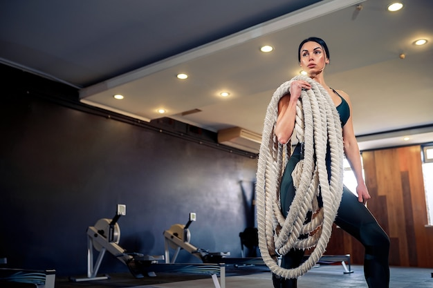 Fit woman dressed in sports outfit posing with battle ropes at gym