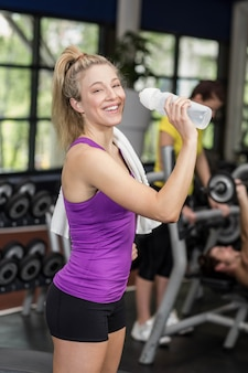 Fit woman drinking from water bottle at the gym
