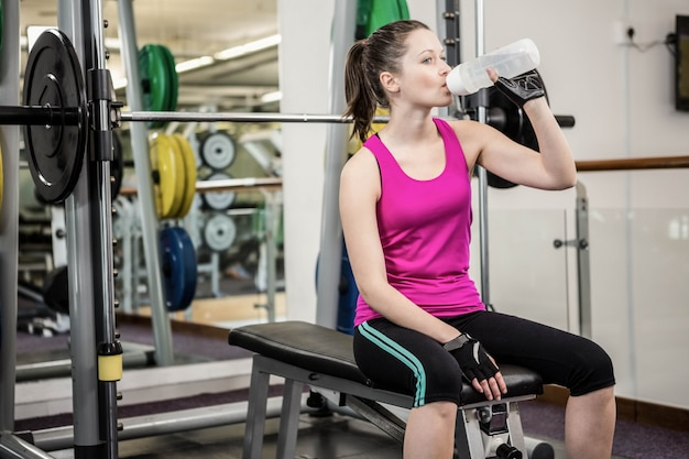 Fit woman drinking water sitting on barbell bench at the gym