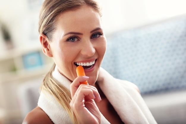 Подходящая женщина ест морковь дома