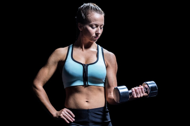 Fit woman exercising by lifting dumbbell against black background