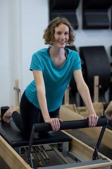 リフォーマーで運動しているフィットの女性